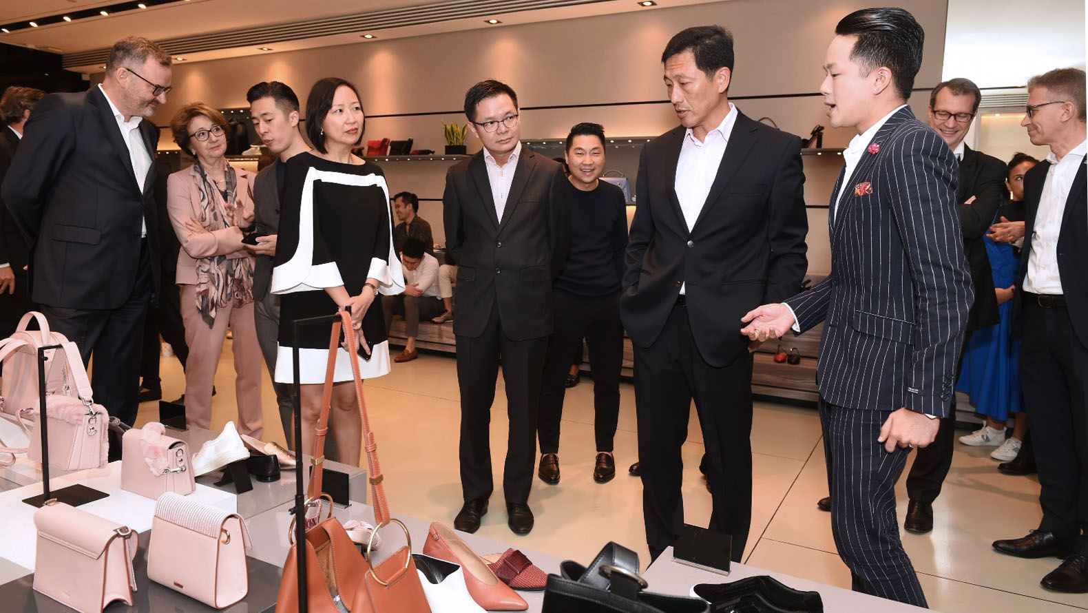 (from right) Fashion coach Nigel Seow from CHARLES & KEITH GROUP demonstrating to Minister Ong how in-house training translates to looks and trends for Charles and Keith Group's fashion stylists, while PCEO Ms Jeanne Liew and SkillsFuture Singapore chief executive Mr Ng Cher Pong look on.